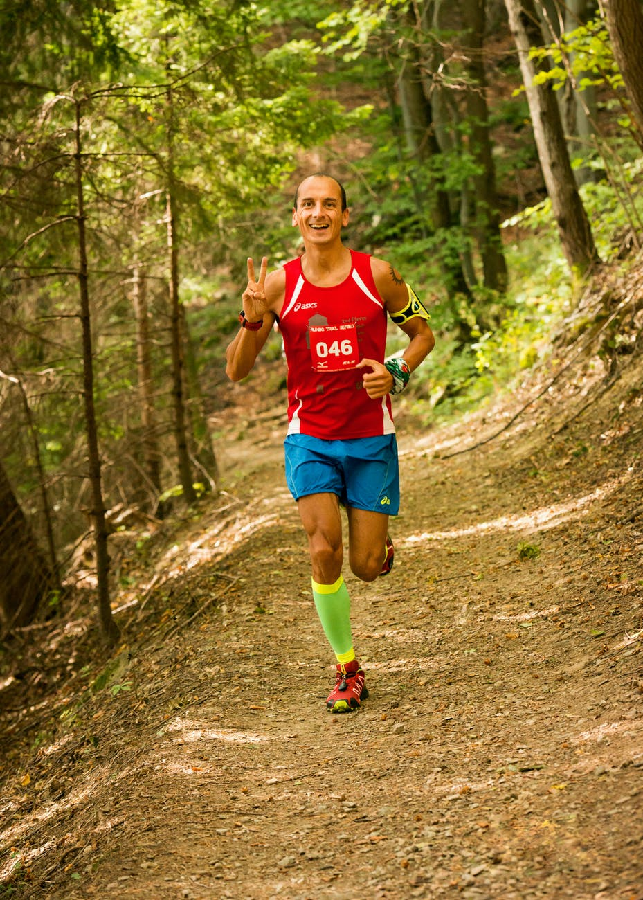 photo of man running in the forest