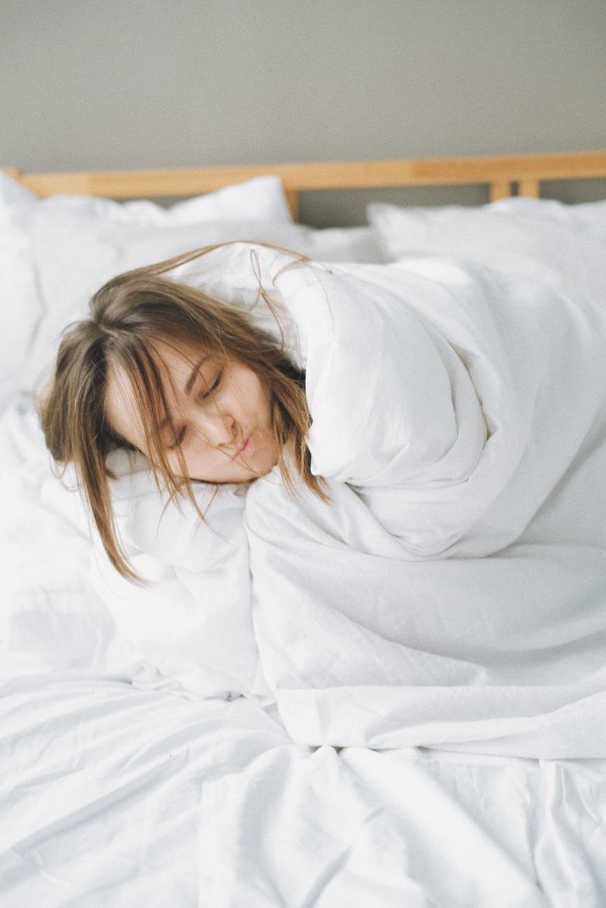 woman covered in white blanket lying on bed